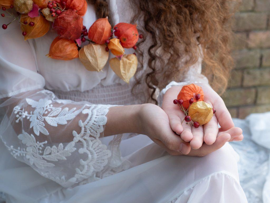 Herfst met oranje physalis in de hand